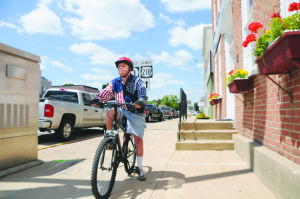 <p>Shelly Steere rides his bike along West Bremer Avenue on Wednesday. He plans to hang out with the RAGBRAI crowd Thursday during the overnight stop.</p>