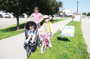 <p>Mom Shelley Armstrong and her kids, Norah, 7, and Gabriel, 5, pose at the trail next to a sign urging Waverly citizens to vote online for a $100,000 grant for dog park in town.</p>