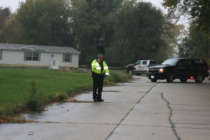 <p>Oelwein Police Chief Jeremy Logan at the scene of Tuesday morning's shooting in northwest Oelwein. The victims' home is in the background</p>