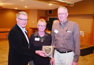 <p>Gene Ficken (left) presents a plaque to the Buchanan County Democrats of the Year Jackie and Chip Hoffman.</p>