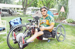 <p>Vern Willey shows off his handcycle, which he has ridden on for 17 of the 24 years he has participated in RAGBRAI.</p>