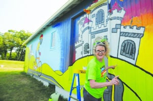 <p>Cyndi Ecker Campbell puts the finishing touches on a mural on the wall of a barn on 12th Street Northwest, which will be the welcoming center when RAGBRAI comes into town on Thursday.</p>