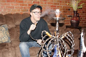 <p>Monte Snyder, owner of Morel's Hookah Lounge, exhales some water vapor after taking a drag from the hookah pipe. The lounge has been open for about three months at 108 W. Bremer Ave., next to Wolf Creek Tattoos.</p>