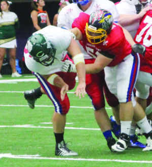 <p>Wapsie Valley's B.J. Weepie sends a defensive lineman to the ground during Saturday's Shrine Bowl a the UNIDome.</p>