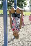 Getting a new perspective on the world is Margarette Carey Elementary first-grader Amalia Djoumessi as she hangs on one of the bars on Tuesday, Aug. 23, 2016, during recess.