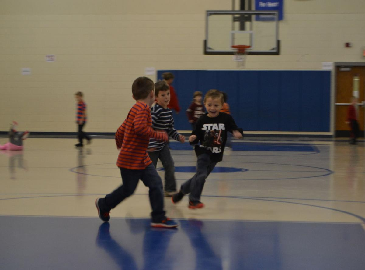 Summit students romp on the current gym floor.