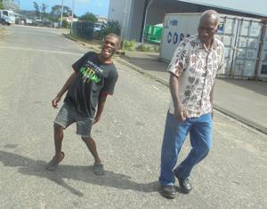 <p>Junior (left) and the Executive Director of the Vanuatu Society of People with Disabilty, Elison Bovu, enjoy a walk at Nambatu in Port Vila</p>