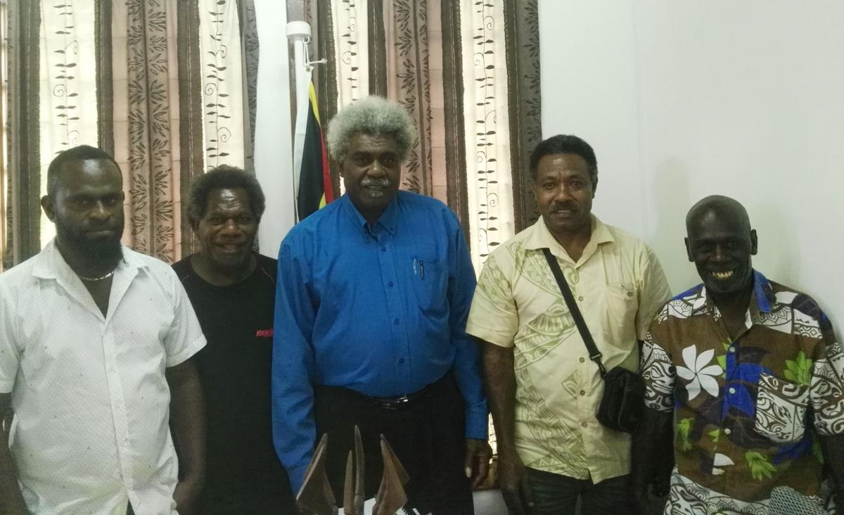 Minister of Education, jean Pierre Nirua, (c) flanked by Members of the School Cooperative Society