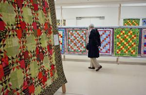 <p>Quilting enthusiasts look over the many quilts on display during the annual Central Washington Quilt Show and Junk-Tiquen In The Burg event at the Kittitas County Fairgrounds, Saturday, April 25, 2015.</p>