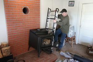 <p>Jeff Douglas, with Armstrong Stove and Spa, installs a new certified energy efficient stove in a home near Thorp, Monday, Feb. 16, 2015. The installation was made possible through a federal and state funded program.</p>
