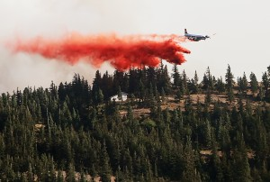 <p>A firefighting aircraft drops fire retardant along a ridge near the Swauk valley area northeast of Cle Elum, in an effort to defend homes from the Taylor Bridge Fire, Tuesday, Aug. 14, 2012. (Brian Myrick / Daily Record)</p>