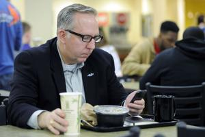 <p>John Calahan, coordinator of space scheduling and utilization for academic affairs at SFA, works via his smartphone during lunch on March 3. Calahan said he primarily uses calendar functions and email on his phone as he dashes from meeting to meeting.</p>