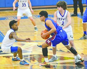 <p><strong>Cameron Fields (1) and Dillion Young (2) of Tivy attempt to trap San Antonio Memorial's Adam Vilanueva Friday night during the Antlers' home win.</strong></p><p><strong></strong></p>