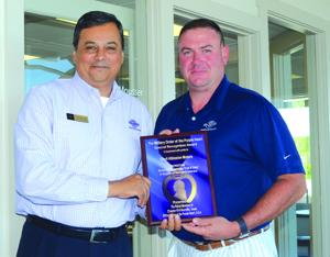<p>Cecil Adkission Motors used cars sales manager Frank Mouser, left, and salesman Jeff Harris show a plaque they recently received from Military Order of the Purple Heart for their company's role in assisting local veterans. </p>