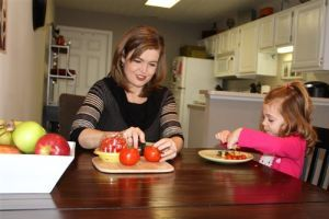 Shannon cuts a tomato for her daughter