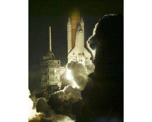 Shuttle blasts off in rare night launch