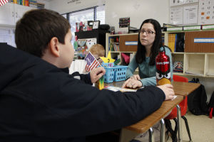 <p>Pieceful Solutions teacher Natalie Dase helps a student with his writing assignment. [Abel Muñiz Jr./Special to Tribune]</p>