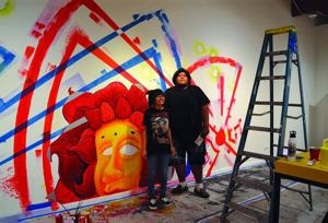 <p>Mentor artist Dwayne Manuel and young artist Ashlee Craig stand next to their recently created mural for <em>Confluence: Inter-generational Collaborations.</em></p>