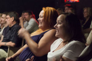 <p>Gilbert resident Melisza Gransbergen (left) and her sister, Jessica Gransbergen, of Phoenix, laugh while the players act out a story they told during the Competitive Comedy Show at the National Comedy Theatre in Mesa on Saturday, May 24, 2014.</p>