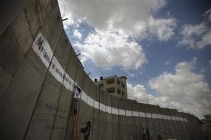 Activists paint graffiti letter on West Bank wall