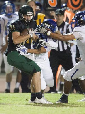 <p>Basha running back Zach Reed (31) is tackled by Chandler cornerback Isiah Swann (25) during the football game between Basha and Chandler at Basha High School on Friday, Oct. 24, 2014.</p>