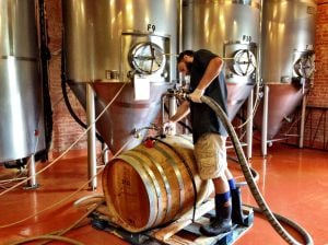 <p>A worker fills one of the barrels of the Saison de Aleatico.</p>