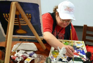 <p>Acrylic artist Jennifer White works on a piece of artwork inside the Arizona Arts Collective Gallery in downtown Mesa, Friday, May 7, 2010.</p>
