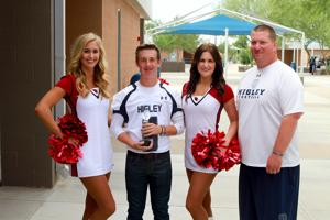 <p><span>Mason Crossland and Higley High School Football Coach Eddy Zubey visit with Cardinals Cheerleaders who delivered a trophy to Crossland when he was named the Cardinals' High School Player of the Week. [Courtesy </span>Higley Unified School District]</p>