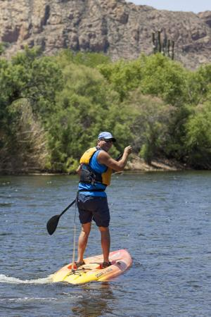 <p>Dennis Wilkins, of Gilbert, paddle boards at the lower Salt River in the Tonto National Forest on Wednesday, May 21, 2014. [GetOut file]</p>