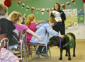 <p>Second-grade students at Nike Elementary School in Catawissa reach out to pet Cooper, the school's certified therapy dog, as he walks around the room during a class with Monica Moore, the school counselor. Moore is Cooper's owner and handler.  </p>