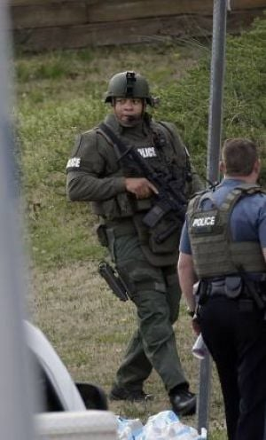 A police officer holds a rifle as he walks near the scene where a man is said to be holding four Gwinnett County firefighters hostage in Suwanee, Ga., April 10, 2013.