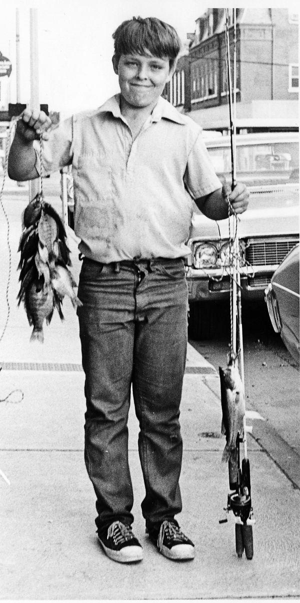 Boy holds many fish on main street