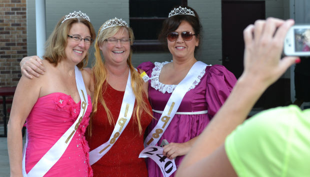 Michelle Reed, left, Kris Westlake and Cheryl Chappelear pose for a photo prior to Saturday's Dash for the Sash in Arlington. The fundraiser for Arlington's post-prom party encourages participants to run or walk in prom attire.