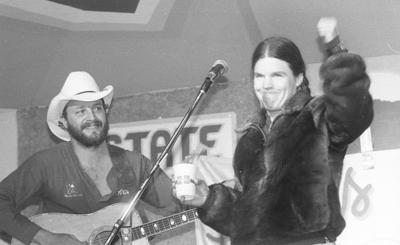 """<p>Hobo Jim and Susan Butcher sing the 'Iditarod Trail Song' on stage at the Alaska State Fair. This photo from the Frontiersman's archive is included in the newly released book """"Iditarod: the First Ten Years.""""</p>"""