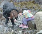 <p>Mount Vernon High School biology student Briana Slater works with kindergarten student Morganne Spain, 6, as they explore the Rosario Beach tide pools area Tuesday, May 19. Scott Terrell / Skagit Valley Herald</p>