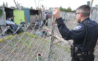 <p>Mount Vernon police oficer Edgar Serrano chats with two men who help manage the community pea patch garden off Kulshan Street. Scott Terrell / Skagit Valley Herald</p>