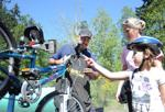 <p>Randy Kaui (left) listens as Raegan Lee, 9, and her mother, Dawn Lee, point out what adjustments he needs to make to Raegan's bike to make it roadworthy at Skagit County Fire District 13's open house on Saturday, May 2, at the Hope Island station in La Conner. Brandy Shreve / Skagit Valley Herald</p>