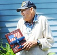 <p>Bill Nowadnick shows off a model of the Chance Vought F4U-1A Corsair plane, which is the type of plane that he flew during WWII as a Marine Corps fighter pilot. Brandy Shreve / Skagit Valley Herald</p>