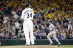 <p>Seattle pitcher Felix Hernandez watches Monday as New York's Mark Teixeira rounds the bases on a grand slam.</p>