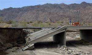 <p>Riverside County Supervisor John J. Benoit takes a photo of a collapsed bridge that was washed out along Interstate 10 in Southern California, Monday, July 20, 2015. All traffic along one of the major highways connecting California and Arizona was blocked indefinitely when the bridge over a desert wash collapsed during a major storm, and the roadway in the opposite direction sustained severe damage. (AP Photo/Nick Ut)</p>