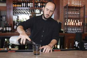 <p>John Stark, bartender at McAdoo's, pours an old fashioned on Feb. 3.</p>