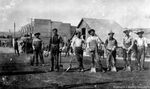 """<p>What we know about this photo: This undated photo donated to the Klamath County Museum in 2012 shows what appears to be a street construction crew. A piece of equipment appears in the background at left. Also in the background is a barn and a brick building with the word """"HARNESS"""" painted on the side. Museum staff speculates the photo was taken on Klamath Avenue or Walnut Street, looking southwest.</p><p>What we don't know: Who are the men in the photo? When and where was this photo taken?</p>"""