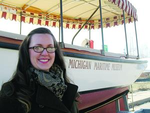 <p>Ashley Deming, new director of education and administration at South Haven's Michigan Maritime Museum, is shown next to the Lindy Lou, an electric-powered river launch owned by the museum.</p>
