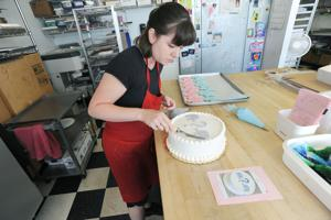 <p>Heidi Sorensen, a cake decorator at The Flour Shop Bakery in Stevensville, decorates a cake containing a blue-cream filling for Katie Metz's gender reveal party.</p>