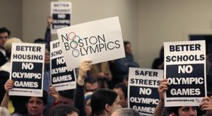 <p>FILE - In this Feb. 5, 2015, file photo, people hold up placards in Boston, against the Olympic Games coming to the city, during the first public forum regarding the city's 2024 Olympic bid. Boston's bid for the 2024 Summer Olympics flamed out in spectacular fashion earlier this week, with local organizers and the U.S. Olympic Committee deciding to part ways after the Boston mayor and the Massachusetts governor refused to be rushed into a decision putting taxpayers on the hook if the games went over budget. (AP Photo/Charles Krupa, File)</p>
