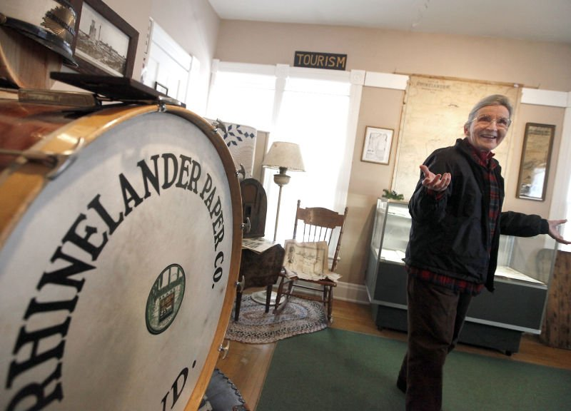 Wausau Paper Mill, June Thiel, curator of Rhinelander Historical Society Museum, shows off bass drum