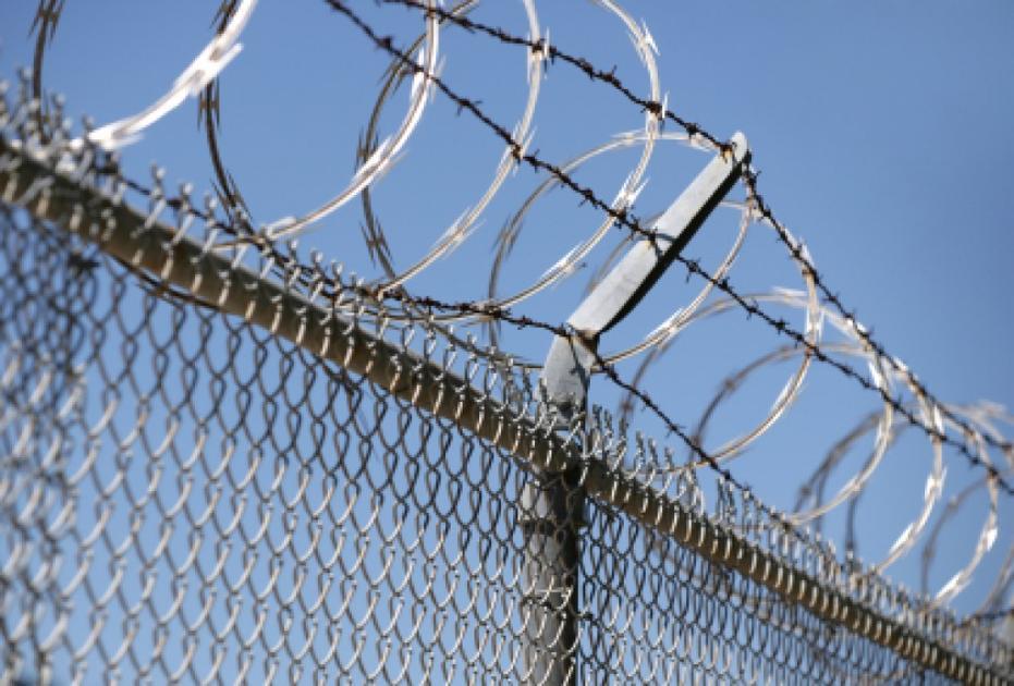 Razor wire chain link fence istock file photo jail prison