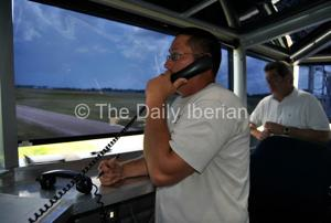 <p>Acadiana Regional Airport air traffic controller Nathan Bourgeois communicates from the temporary 'control tower,' which is actually a mobile facility the airport is renting, as ARA Director Jason Devillier observes in background. The facility is being used until the ARA completes renovations to its tower.</p>