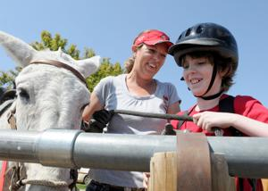 <p>Trinity Jackson, director of Heart 2 Heart Ranch, watches Sam Lee, 11, of Parma, tie a proper knot after riding Rodebud at the Ranch outside Parma. Riding mules at the ranch has helped many kids with self-esteem and physical disabilities. This is the first year Heart 2 Heart Ranch has participated in Idaho Gives, a program of the Idaho Nonprofit Center. Friday, May 1, 2015 Adam Eschbach/IPT</p>