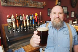 <p>Jerry Fergusson, the Crescent Brewery owner, holds up a pint of the amber ale at the Nampa brewery located at 1521 Front Street. Tuesday, March 10, 2015 (Greg Kreller/IPT)</p>